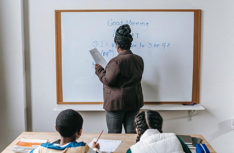 Math teacher writing on the board.
